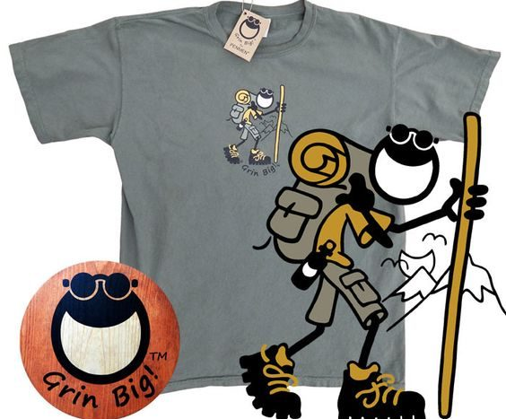 Gray t shirt with a picture of a man hiking that says Grin Big!