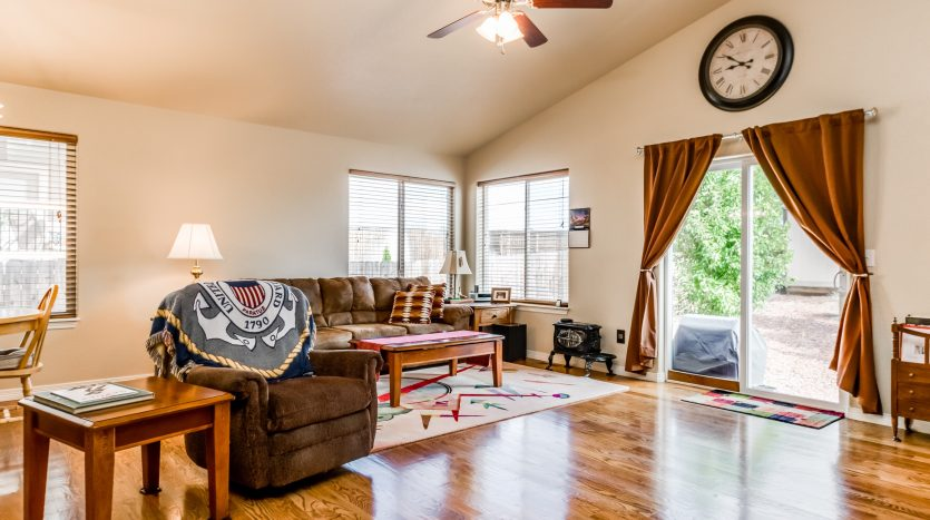 Picture of a family room with light shining on the medium colored wood floor