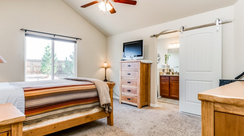 Picture of a bedroom with a striped bedspread on the bed, a ceiling fan, looking into the master bathroom which has barn doors