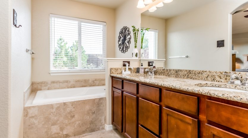 Marble countertop in a bathroom with tan tile, natural light from window next to tub