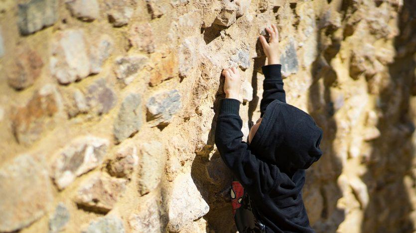 Young boy in black sweatshirt, climbing rock call, reaching high