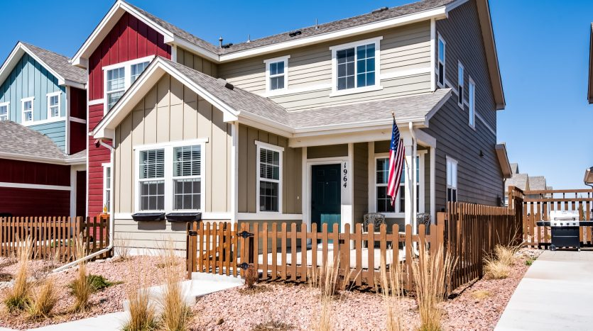 Cream colored painted front of home for sale entrance with brown picket fence and American flag