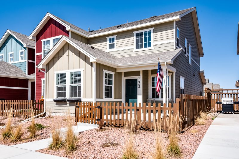 Cream colored front home for sale entrance with brown picket fence and American flag